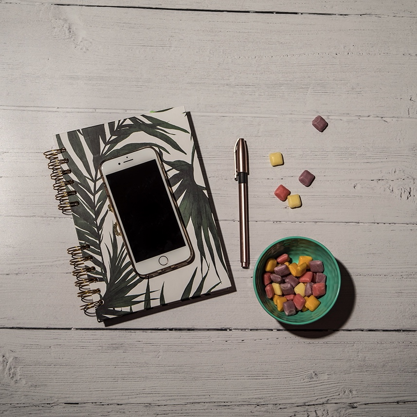 Mobile phone resting on notepad with pen and sweets beside it.