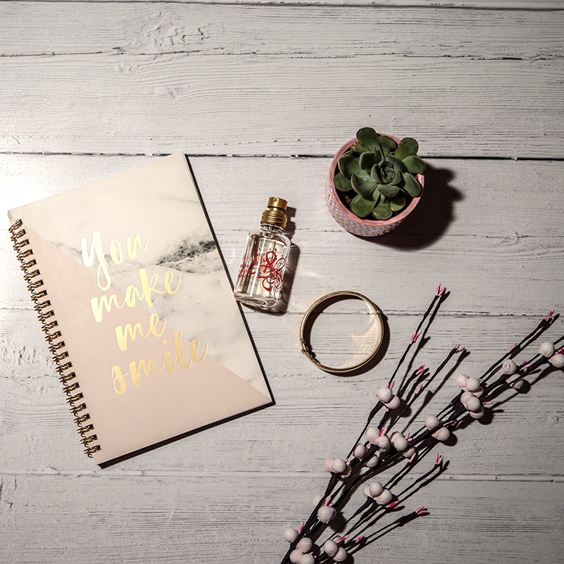 Simple steps to the ideal self care road trip - flat lay including note book, plants and perfume