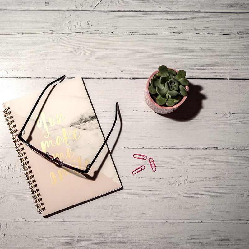 Maintain your self care routine - image is of a flatlay overlooking a notebook and glasses next to a cactus plant